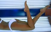 image of suntanning  - Beautiful slim blonde girl tans in the solarium - JPG