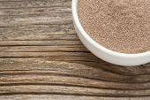 teff flour - a ceramic bowl on grained wood background