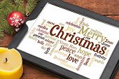 stock photo of christmas song  - cloud of words or tags related to Christmas on a  digital tablet with a candle and Xmas decorations - JPG
