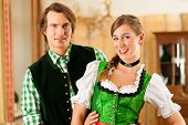 Young couple in traditional Bavarian Tracht in restaurant or pub, they might be the innkeepers