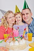 Mother, father and little daughter sit cheek to cheek at birthday table