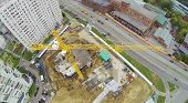 Yellow crane at construction site near residential complex. View from unmanned quadrocopter.