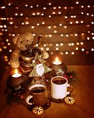 Christmastime decoration, beautiful festive still life on the table on glowing wall background, cups of tea with traditional Christmas gingerbread