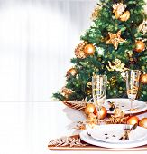 Christmas dinner decoration, fresh green fir tree decorated with shiny golden baubles, festive table setting, New Year celebration at home, greeting card with copy space