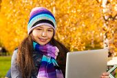 pic of 11 year old  - Girl with tablet computer 11 years old sitting in the park on sunny autumn day