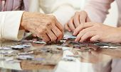 Old hands solving jigsaw puzzle in a nursing home
