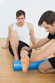 picture of physical therapist  - Physical therapist examining a young mans leg at the hospital gym - JPG