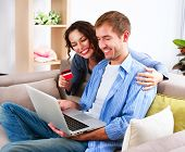 Online Shopping. Happy Smiling Couple Using Credit Card to Internet Shop. Young Family with laptop and credit card buying online. Christmas and New Year Gifts. e-shopping