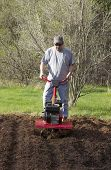 Man Gardening With Rototiller
