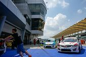 SEPANG, MALAYSIA - MAY 11, 2014: Marshals push the cars in for weighing after the Touring Car Series Asia race, as part of the Malaysian Super Series Rd 2 held at the Sepang International Circuit.