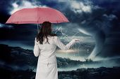 Businesswoman holding umbrella against stormy sky with tornado over landscape