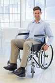 Casual businessman in wheelchair smiling at camera in the office