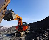 stock photo of iron ore  - loading of iron ore in career Excavator in railway carriages on the extracted minerals - JPG