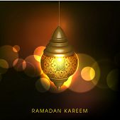 Illuminated golden arabic lamp or lantern on shiny brown background, creative greeting card design f