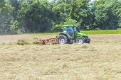 Tractor In Meadow Making Hay