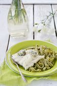 Codfish fillet and pasta on the green plate.
