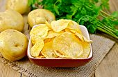 Chips In Bowl With Potatoes On Sacking And Board