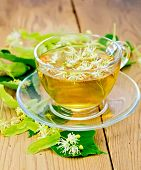 pic of linden-tree  - Herbal tea from linden flowers in a glass cup fresh linden flowers on a wooden board - JPG