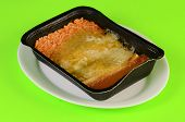 stock photo of enchiladas  - Frozen microwave Mexican Dinner in black plastic tray on white plate against lime green background - JPG