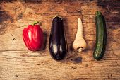 stock photo of parsnips  - Red pepper aubergine parsnip and courgette on a wooden table - JPG
