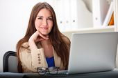 woman sitting with laptop computer smiling in office