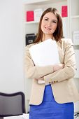 young smiling woman holding blank, paper in office