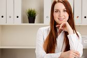 Close-up portrait of young businesswoman in bright office