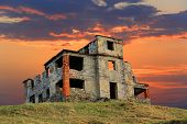 Ruins of old abandoned house on sunset background