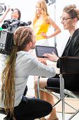 Director giving cameraman shoot or scene direction on set of a video production for TV, television o