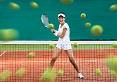 Sports woman returning lots of balls at the tennis court. Concept of tournament preparation and heal