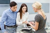 stock photo of jewel-case  - Consultant helps couple to choose jewelry at jeweler - JPG