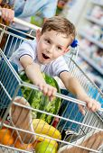 Little boy sits in the cart with watermelon and other products bought by parents