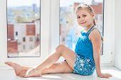 Girl In Blue Dress Sitting On Window Sill In Sun Light