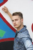 Attractive Young Blond Man Against Colorful Graffiti Wall