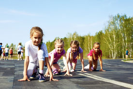 pic of pre-teens  - four pre-teen girls starting to run on track