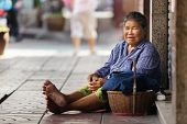 BANGKOK, THAILAND, DECEMBER 16, 2012 : Thai woman beggar sitting on the sidewalk in the Chinatown district in Bangkok, Thailand.