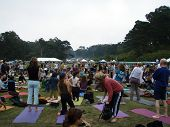 Group Of People Gather To Do Yoga Outdoors At Power To The Peaceful 2007 Music Festival
