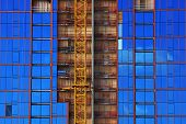 Blue Glass Windows Reflect Clouds With Red Lines Framing Windows And Yellow Crane Metal Shaft