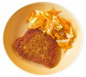 Cutlet with grated carrots on ceramic dish.