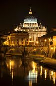 Monumental St. Peters Basilica over Tiber at night in Rome, Italy.