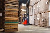 Reach truck forklift lifting a pallet from the top shelf in a large warehouse