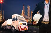 Engineer Holding Hard Hat Standing Against Beautiful Lighting Of Oil Refinery In Heavy Petrochemical