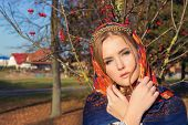 beautiful young tender graceful girl in colored scarf on her head with a beautiful gold band