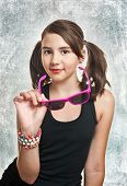 Portrait of cute teen girl with pony tails and sun glasses looking at camera, on textured background