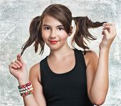 A beautiful teen girl in black top with pigtails. Portrait of smiling girl with two pigtails