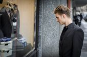 stock photo of boutique  - Handsome Young Man in Black Elegant Suit Looking at Displayed Fashion Items in Glass Window Boutique at the Street Side - JPG
