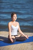 foto of breathing exercise  - Young woman performs a set of breathing and stretching exercises for beginners yoga on the beach on a summer day - JPG