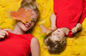 Beautiful Woman And Child On Yellow Autumn Leaves