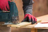Carpenter Sawing A Board