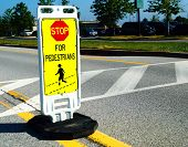 picture of pedestrian crossing  - A Stop for Pedestrians sign marks a crosswalk in an office parking lot - JPG